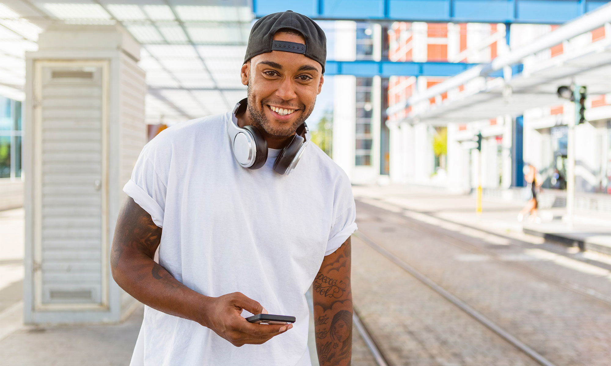 Smiling young man with headphones and smartphone waiting at tram stop.